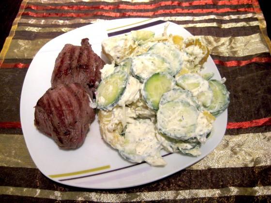 Rosarot gebratenes Steak, serviert mit cremigem Kartoffel-Gurkensalat, verfeinert mit Oregano und Petersilie